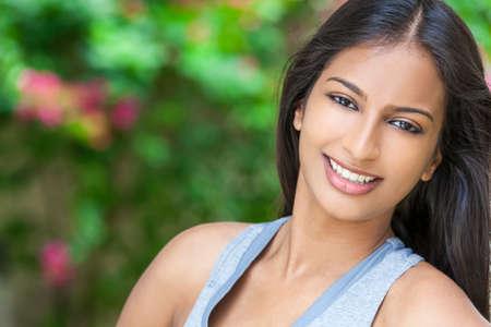 sonriente: Retrato al aire libre de una hermosa mujer joven asiática india o niña al aire libre en sol de verano con los dientes perfectos y el pelo largo
