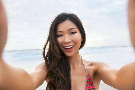 girl blowing: Asian young woman or girl in bikini, taking vacation selfie photograph at the beach Stock Photo