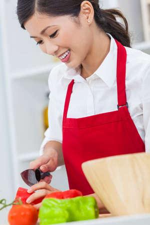 cooking healthy: Una hermosa mujer joven feliz asi�tica china o ni�a que llevaba un delantal rojo de corte y preparaci�n de comida fresca ensalada de verduras en su cocina en casa