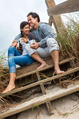 asian adult: Young Asian Chinese man & woman, boy & girl, couple sitting on wooden steps overlooking a beach drinking mugs of tea or coffee