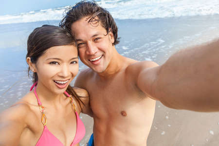 japanese people: Man & woman Asian couple, boyfriend girlfriend in bikini, taking vacation selfie photograph at the beach Stock Photo