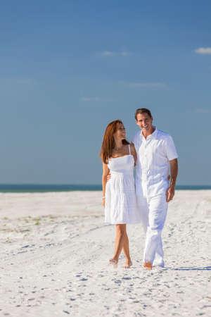 parejas caminando: Romántica hombre y mujer pareja romántica en la ropa blanca caminando en una playa tropical desierta con brillante cielo azul claro