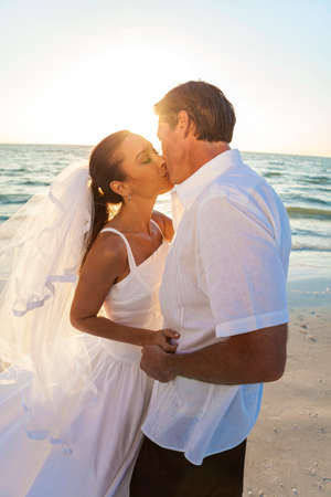 hot kiss: A married couple, bride and groom, kissing sunset sunrise on a beautiful tropical beach
