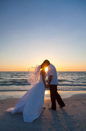 beach kiss: A married couple, bride and groom, kissing at sunset sunrise wedding on a beautiful tropical beach Stock Photo