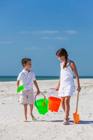 bucket and spade: Happy children, boy girl, brother and sister having fun walking and playing in the sand on a beach with bucket and spade Stock Photo