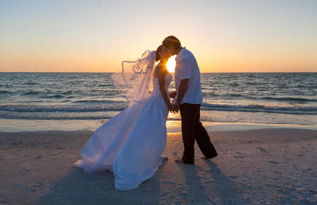 bride: A married couple, bride and groom, kissing at sunset or sunrise on a beautiful tropical beach