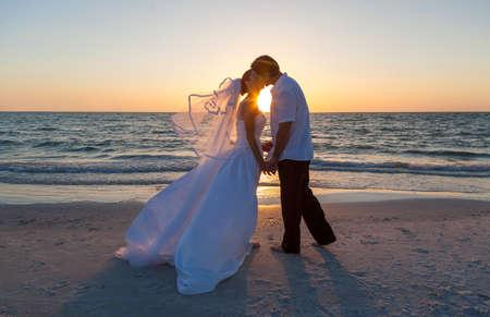 Een echtpaar, bruid en bruidegom, kussen bij zonsondergang of zonsopgang op een mooi tropisch strand Stockfoto