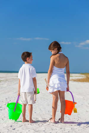 bucket and spade: Rear view of happy children, boy girl, brother and sister having fun playing in the sand on a beach with bucket and spade Stock Photo