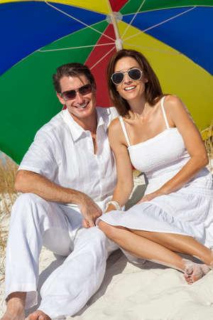 femme romantique: Homme et femme romantique couple sous un parapluie de couleur soleil multi ou parasol sur une plage Banque d'images