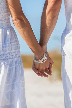 romantic sky: Rear view of man and woman romantic couple in white clothes holding hands on a deserted tropical beach with bright clear blue sky