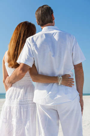 romantic sky: Rear view man and woman romantic couple embracing on a deserted tropical beach with bright clear blue sky