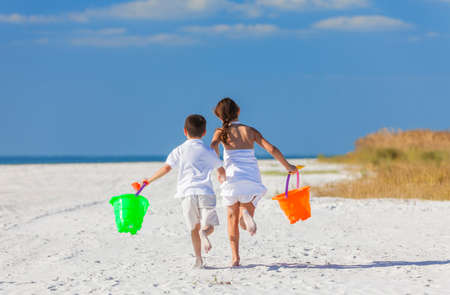 boy shorts: Happy children, boy girl, brother and sister running and having fun playing in the sand on a beach with bucket and spade