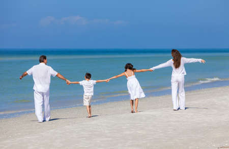 Rear view of happy family of mother, father and two children, son and daughter, walking holding hands and having fun in the sand on a sunny beach