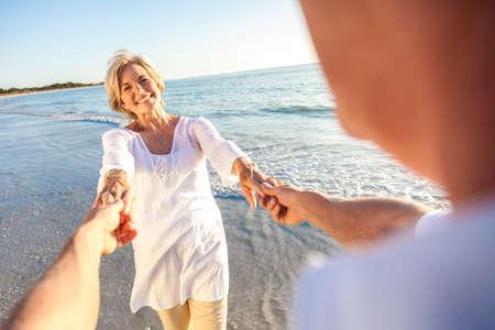 Gelukkig senior man en vrouw paar wandelen of dansen en hand in hand op een verlaten tropisch strand met helder blauwe hemel Stockfoto