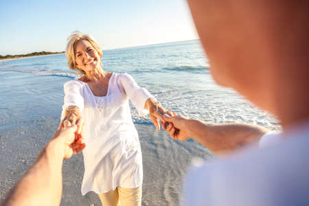 Happy senior man and woman couple walking or dancing and holding hands on a deserted tropical beach with bright clear blue sky Standard-Bild