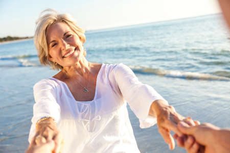 aging: Happy senior man and woman couple walking or dancing and holding hands on a deserted tropical beach