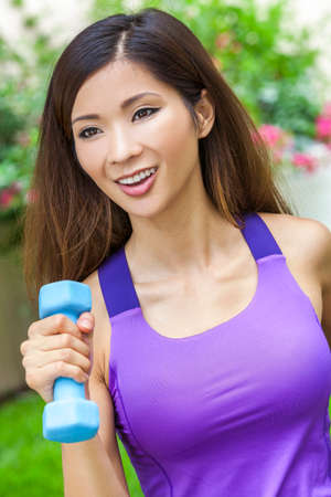 chinese lady: Beautiful Chinese Asian young woman or girl running exercising with weights outside in summer sunshine with perfect teeth and long hair