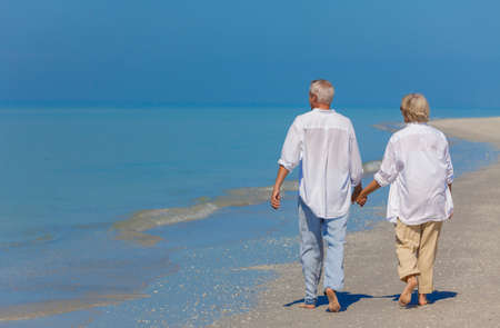 Senior man and woman couple holding hands walking on a deserted beach Imagens