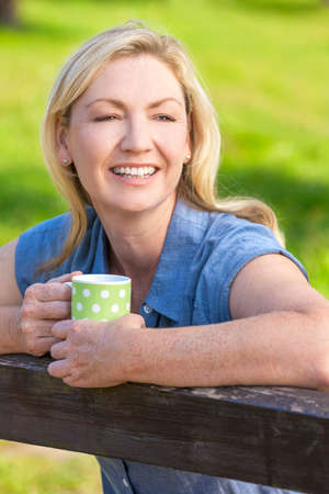 thirties: Beautiful happy middle aged woman in her thirties or forties smiling and leaning on fence in sunshine drinking tea or coffee