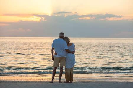 parejas romanticas: Senior hombre y mujer pareja abrazando al atardecer o amanecer en una playa tropical desierta