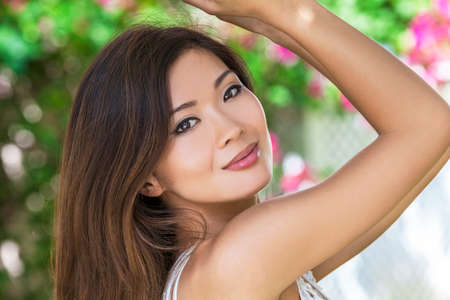 Outdoor portrait of a beautiful young female Chinese Asian young woman or girl Stock Photo