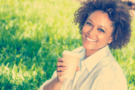 mixed race woman:  a beautiful young mixed race black African American woman smiling and drinking a takeaway cup of coffee outside