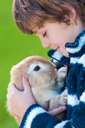 boys playing: Young male boy child outside playing with his pet rabbit