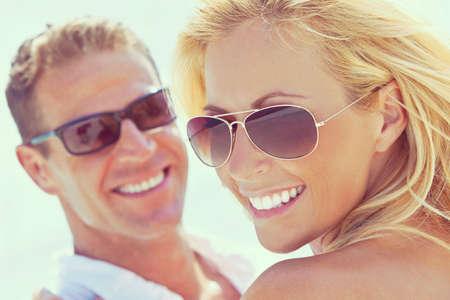 Fotografía de feliz y atractiva pareja de hombre y mujer con gafas de sol y sonriendo al sol en la playa