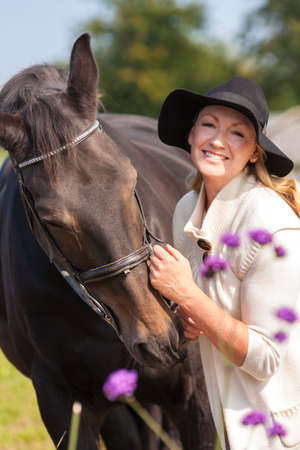 mid thirties: Beautiful happy middle aged woman wearing black floppy hat, smiling and stroking her horse in sunshine