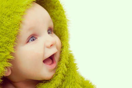 mouthed: Instagram style photograph of beautiful smiling baby wrapped in a furry green blanket