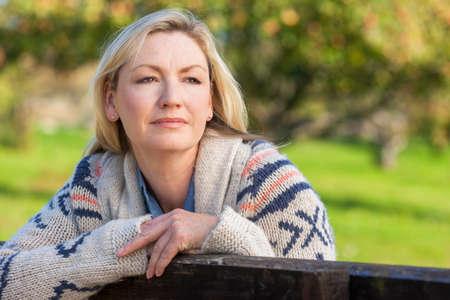 Attractive réfléchie femme d'âge moyen se penchant reposant sur une clôture dans la campagne Banque d'images - 47468681