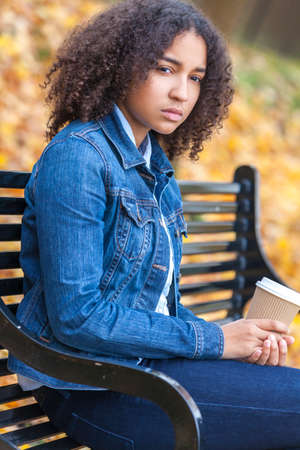 Sad thoughtful or depressed mixed race African American girl teenager female young woman drinking takeaway coffee outside sitting on a park bench in autumn or fall Stockfoto