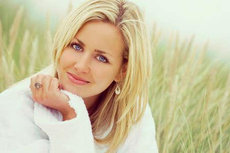 ragazze bionde: fotografia di una bella bionda ragazza dagli occhi blu o giovane donna che indossa un abito bianco spugna seduta in erba alta