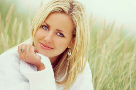 nature:   photograph of a beautiful blond haired blue eyed girl or young woman wearing a white towelling robe sitting in tall grass