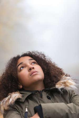 mujer triste: Una triste pensamiento niña mestiza pensativa hermosa afroamericano o una mujer joven mirando hacia arriba al aire libre en un día de niebla o niebla Foto de archivo