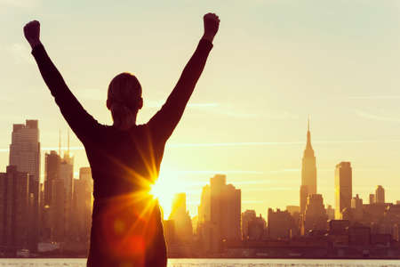 early morning:  silhouette of a successful woman or girl arms raised celebrating at sunrise or sunset in front of the New York City Skyline