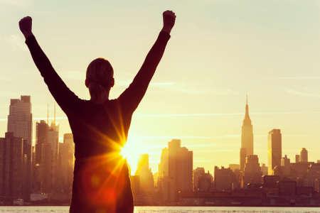 exito: silueta de una mujer o niña con éxito los brazos levantados celebrando al amanecer o al atardecer frente a la ciudad de Nueva York Skyline