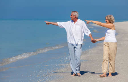 pointing: Happy senior man and woman couple walking, holding hands and pointing to sea on a deserted tropical beach with bright clear blue sky