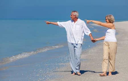 señora mayor: Hombre mayor feliz y mujer pareja caminando, tomados de la mano y apuntando a la mar en una playa desierta tropical con brillante cielo azul claro