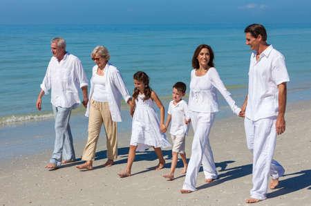 abuelos: Una familia feliz de madre, padre, abuelos y dos hijos, hijo e hija, caminando tomados de la mano y divertirse en la arena de una playa soleada