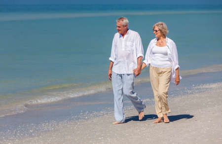 senior woman: Happy senior man and woman couple walking and holding hands on a deserted tropical beach