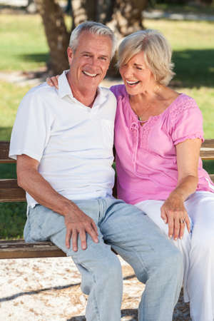 seniors laughing: Happy senior man and woman couple sitting laughing together on a park bench outside in sunshine Stock Photo