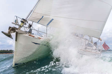 Close up on the bow of a sailboat breaking through a wave Stock Photo