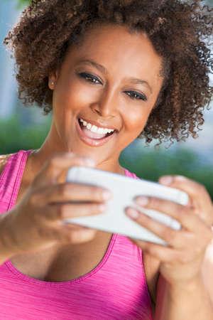 rosa negra: Raza mixta mujer joven afroamericano o ni�a que toma la fotograf�a selfie usa smartphone o tel�fono celular Foto de archivo
