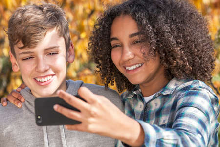 interracial love: Mixed race group of two happy children teenagers, African American girl caucasian boy laughing together and taking selfie photograph on cell phone smartphone