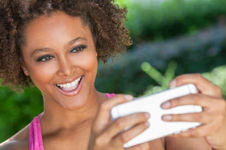 women black: Raza mixta mujer joven afroamericano o ni�a que toma la fotograf�a selfie usa smartphone o tel�fono celular Foto de archivo
