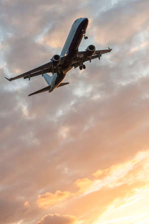 air plane: A modern commercial airplane or airliner flying at sunrise or sunset