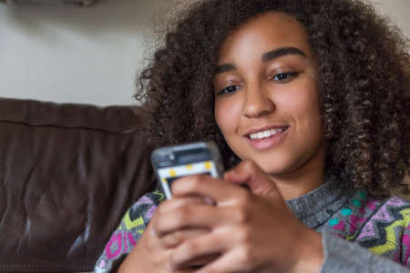 cell: Beautiful happy mixed race African American girl teenager female child smiling with perfect teeth and texting sending text message on cell phone