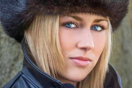 cabello rubio: Retrato del invierno de la mujer naturalmente hermosa en su veintena con cabello rubio, los dientes perfectos y ojos azules con guantes sombrero de piel y abrigo de cuero