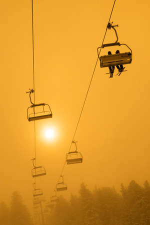 chair on the lift: People on ski chair lift at misty sunset or sunrise Stock Photo